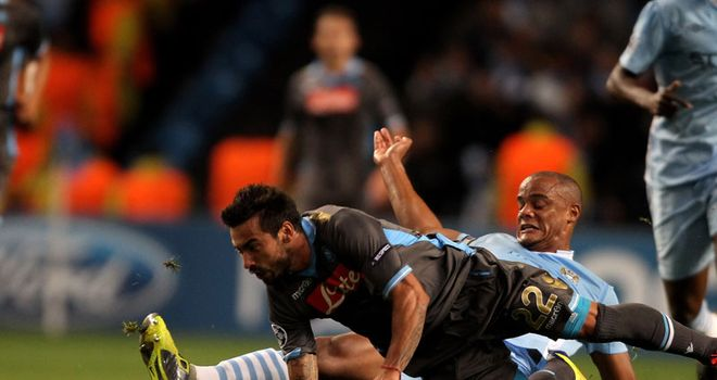 Slide and tested: Kompany gets stuck into Ezequiel Lavezzi at the Etihad Stadium
