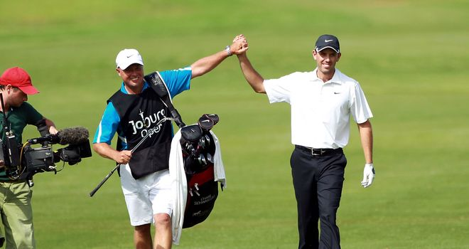 Charl Schwartzel celebrates with his caddie as he prepares to wrap up last year's event