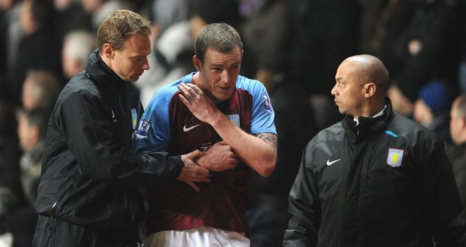Richard Dunne is forced off against Manchester City with an apparent dislocated shoulder