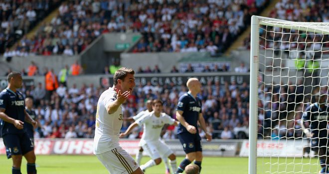 Angel Rangel fires Swansea in front with a little hand from West Ham keeper Jussi Jaaskelainen
