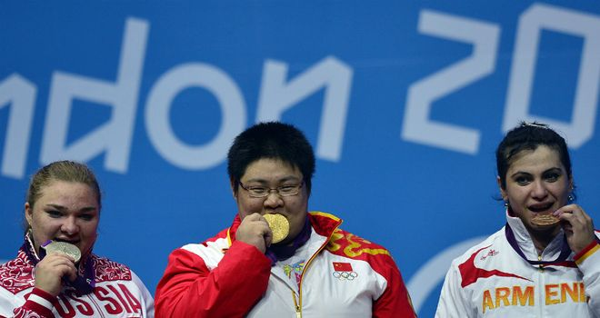 Zhou Lulu (C) poses with her gold medal alongside Tatiana Kashirina (L) and Hripsime Khurshudyan (R)