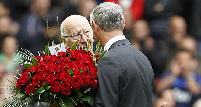 Sir Bobby Charlton hands over flowers to Ian Rush before the match at Anfield