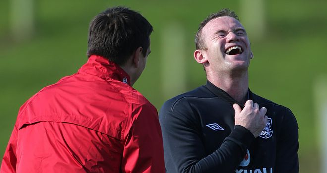 Wayne Rooney shares a joke with England coach Gary Neville