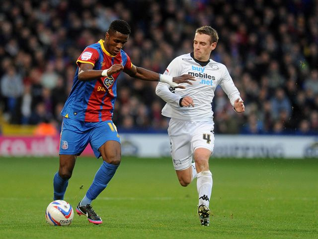 Wilfried Zaha and Craig Bryson battle for the ball
