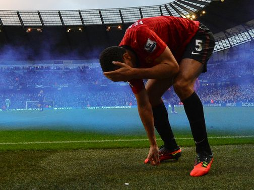 Rio Ferdinand grabs his head after being struck