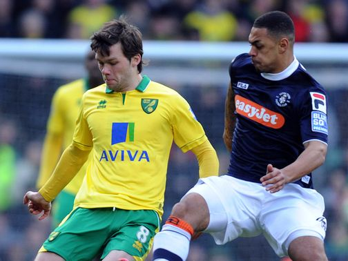 Jonny Howson is challenged by Andre Gray