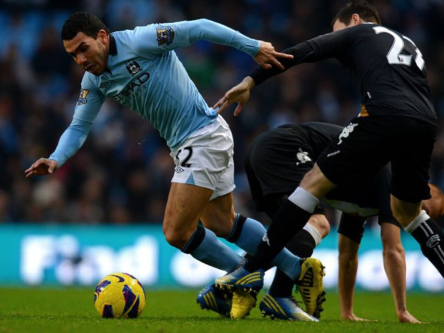 Carlos Tevez tries to wriggle his way through