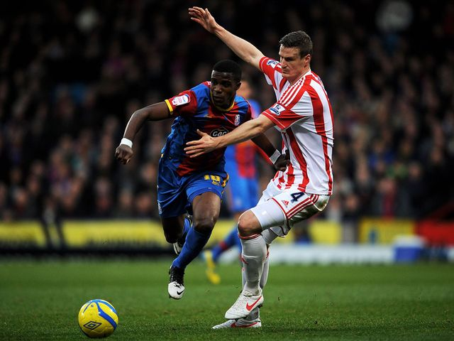 Wilfried Zaha competes with Robert Huth