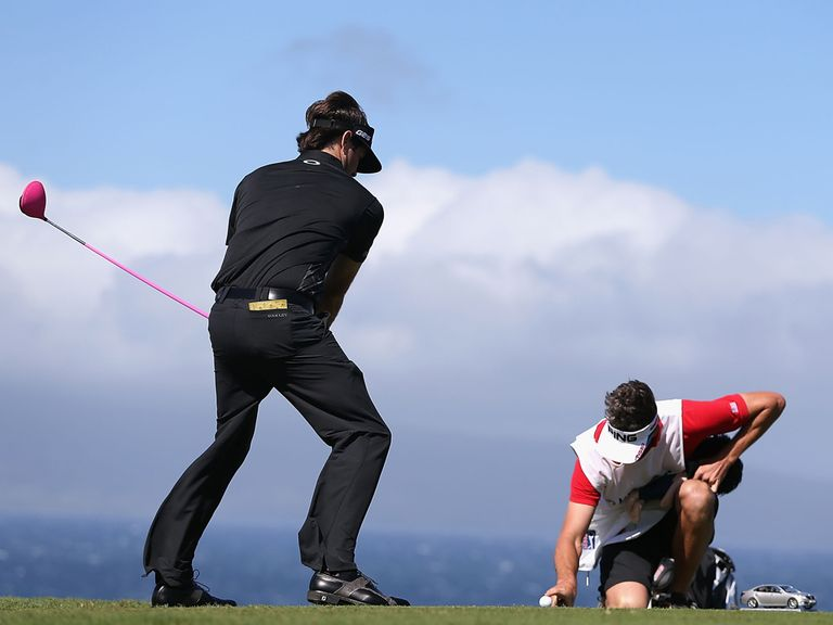 Bubba Watson pretends to tee off while his caddie holds the ball still