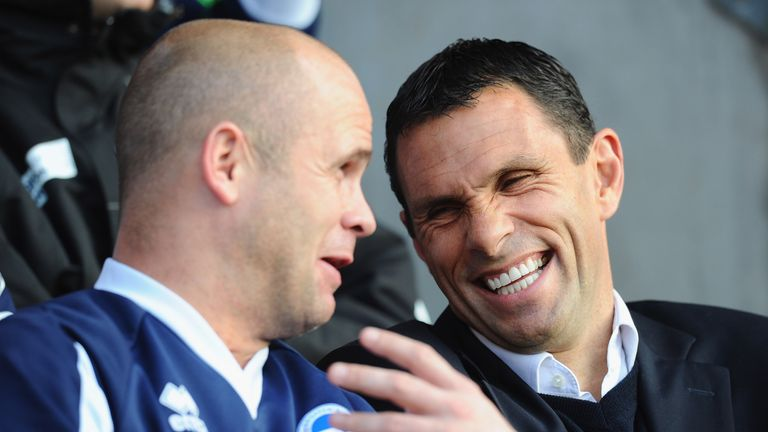 Brighton manager Gus Poyet shares a joke with assistant Charlie Oatway