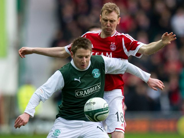 Paul Cairney is kept in check by Stephen Hughes.