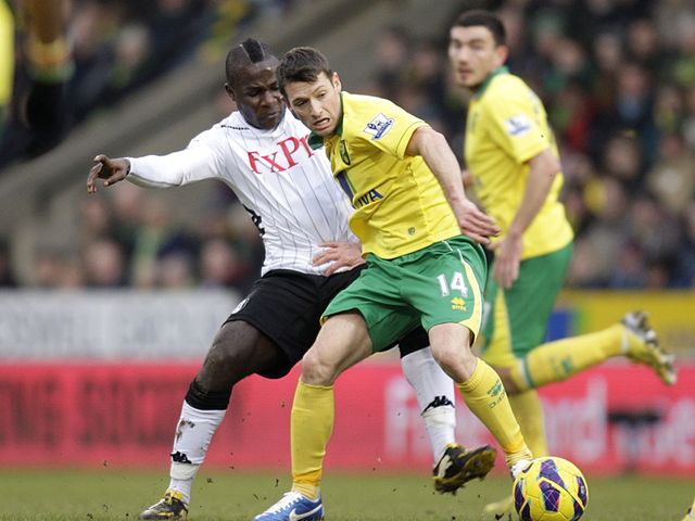 Wesley Hoolahan and Emmanuel Frimpong battle for the ball