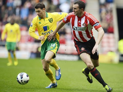 Wes Hoolahan and John O'Shea battle for the ball