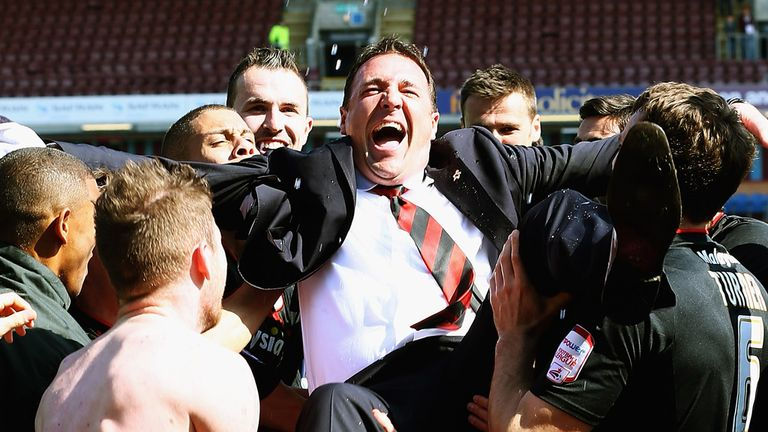 Malky Mackay is thrown in the air by his Cardiff City players after clinching the Championship title at Burnley