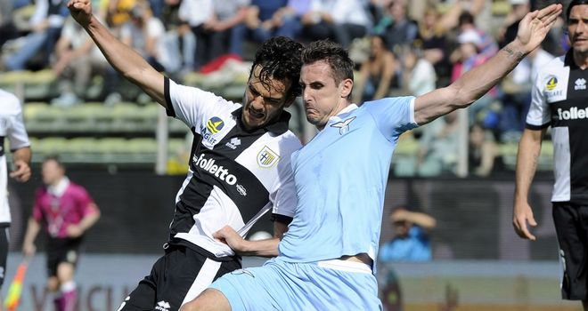 Marco Parolo and Miroslav Klose slide in for the ball