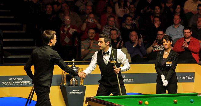 Ronnie O'Sullivan shakes hands with Judd Trump after completing a 17-11 victory