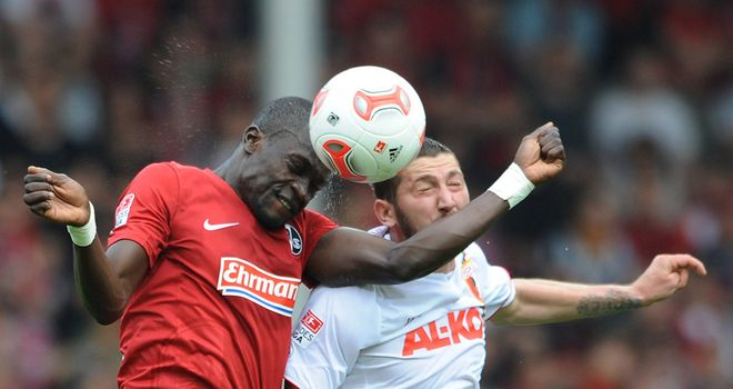 Fallou Diagne of Freiburg and Sascha Moelders of Augsburg contest a header