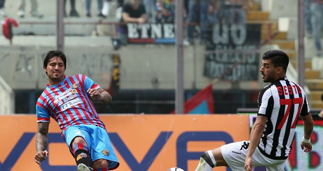 Pablo Alvarez of Catania tries to play the ball past Alessio Sestu of Siena