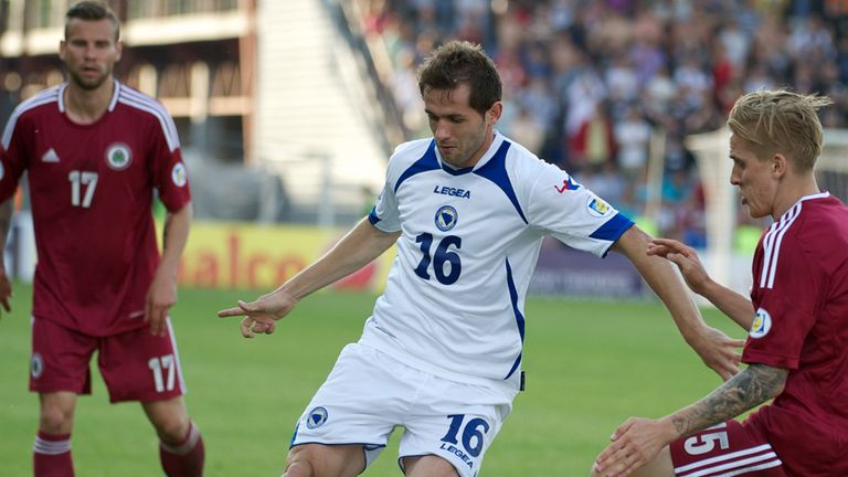 Senad Lulic looks to hold off Latvia's Artis Lazdins