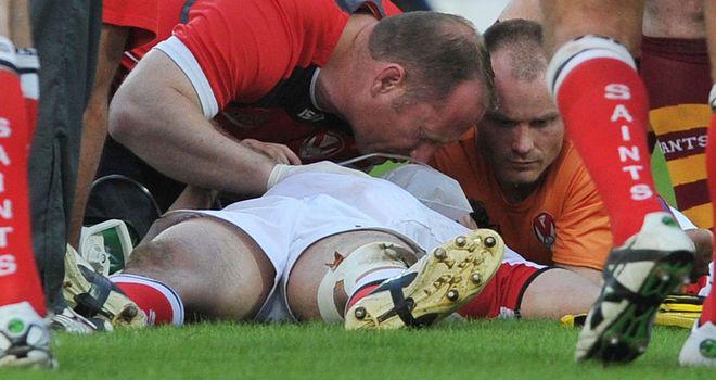 Ade Gardner lies injured on the turf at the John Smith's Stadium on Monday