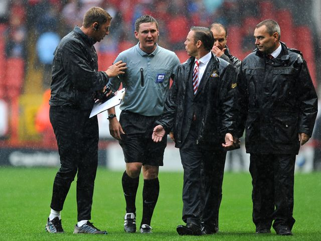 Doncaster boss Paul Dickov talks to the referee.
