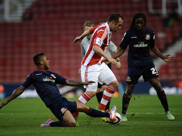 Charlie Adam of Stoke is tackled by Ashley Hemmings