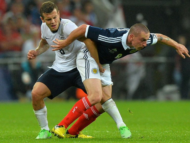 Jack Wilshere tangles with Scott Brown.
