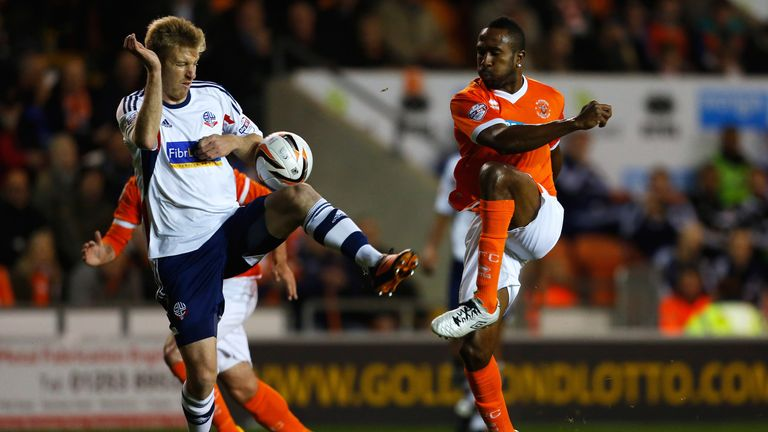 Blackpool's Ricardo Fuller is challenged by Tim Ream of Bolton