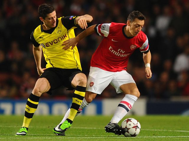 Mesut Ozil holds off Robert Lewandowski