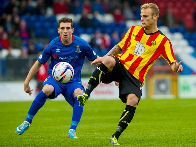 Kallum Higginbotham is closely watches by Graeme Shinnie.