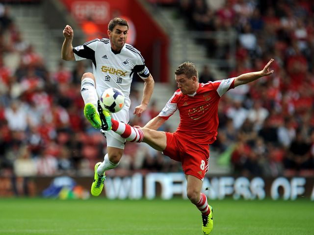 Angel Rangel and Steven Davis battle for the ball