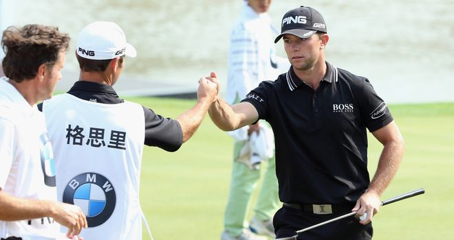 Luke Guthrie celebrates with his caddie after his opening 65