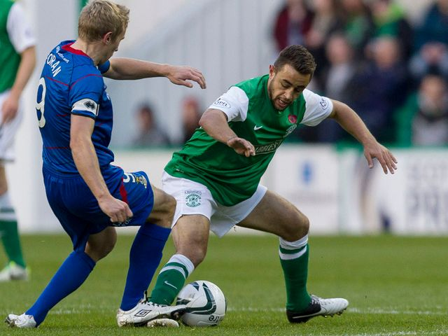 Richie Foran left challenges Hibernian's Tom Taiwo