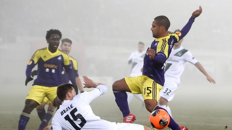 Swansea winger Wayne Routledge is challenged by Stephane Besle