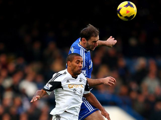 Branislav Ivanovic and Wayne Routledge go for a high ball