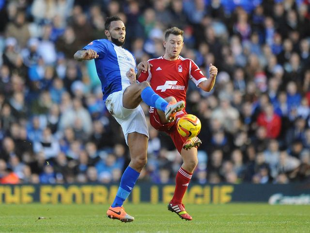 Kyle Bartley and Simon Cox battle for a bouncing ball