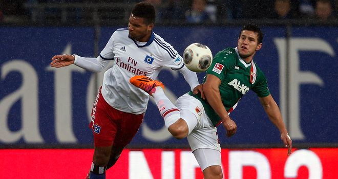 Jonathan Tah (left) of Hamburg and Raul Bobadilla of Augsburg compete