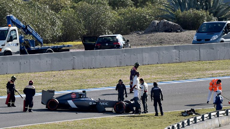 Adrian Sutil inspects his crashed car