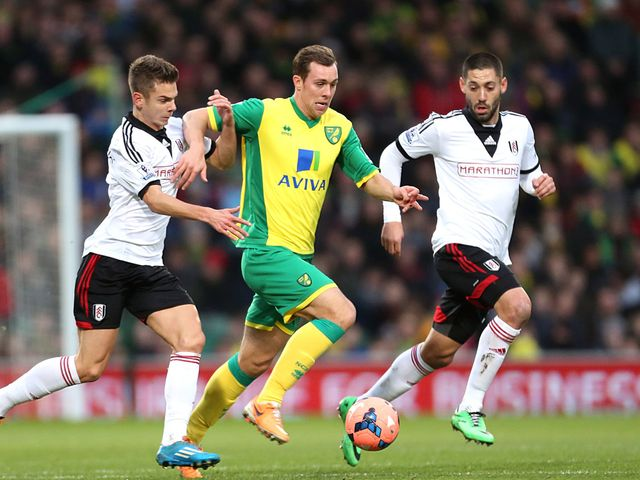 Norwich City's Steven Whittaker takes on Fulham players