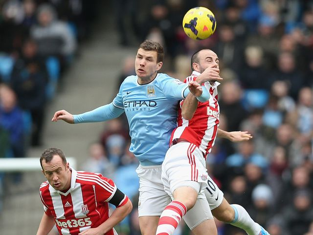 Marc Wilson of Stoke City in action with Edin Dzeko of Man City