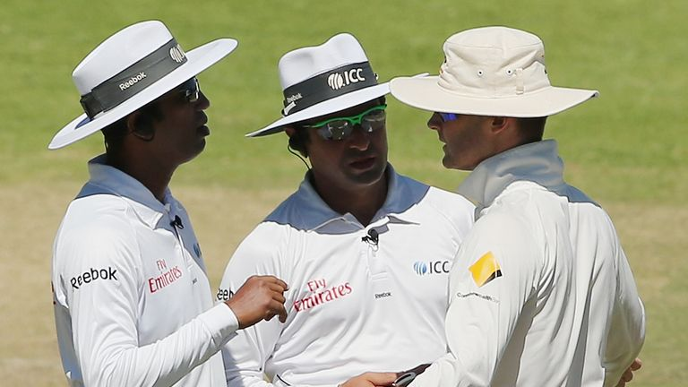 Umpires Kumar Dharmasena and Aleem Dar speak to Michael Clarke