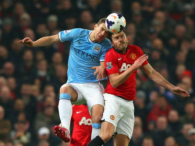 Michael Carrick and Edin Dzeko challenge for a header