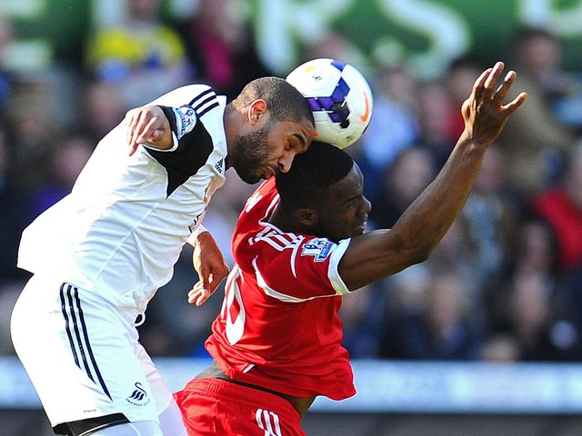 Victor Anichebe and Ashley Williams go for a header