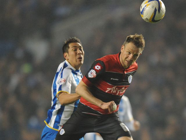 Clint Hill heads the ball away from Leonardo Ulloa