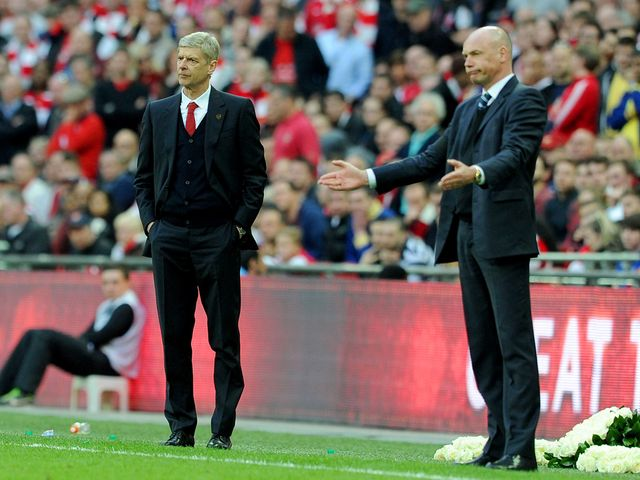 Arsene Wenger and Uwe Rosler watch the action