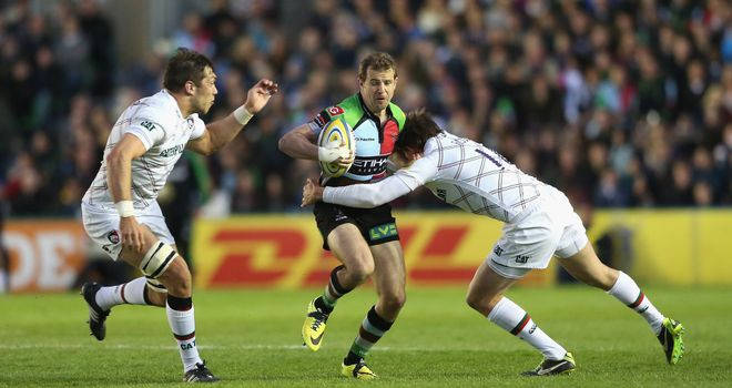 Nick Evans of Harlequins is tackled by Leicester's Toby Flood