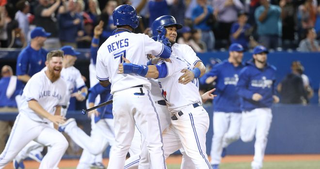 Kevin Pillar is mobbed after he scored the winning run against Tampa Bay Rays