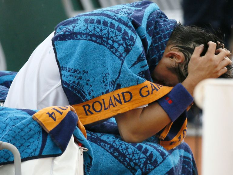 Kei Nishikori holds his head in his hands