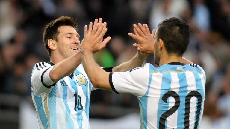 Argentina's forward Lionel Messi (I) celebrates with Sergio Aguero after scoring against Slovenia during a friendly