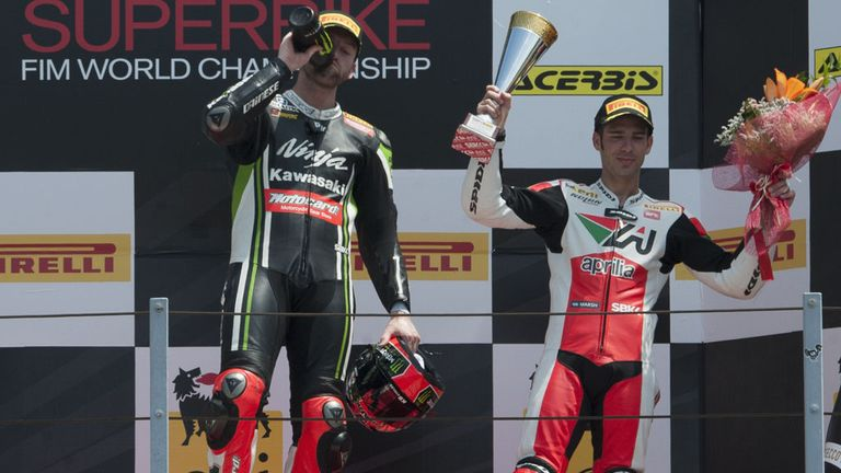 Winner Tom Sykes enjoys his bottle of champagne while third-placed Marco Melandri waves to the crowd at Misano